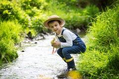 Słodki dziecko, bawić się na małej rzece z kaczątkami Obraz Royalty Free