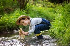 Słodki dziecko, bawić się na małej rzece z kaczątkami Fotografia Stock