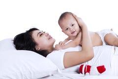 Słodki dziecko bawić się z jej mamą odizolowywającą zdjęcie royalty free