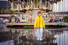 Słodki dziecko, chłopiec dopatrywania carousel w deszczu, jest ubranym kolor żółtego r Obrazy Royalty Free