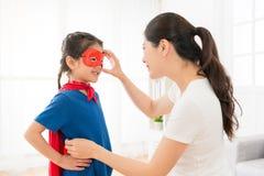 Słodki dziewczyna dzieciak jest ubranym czerwoną peleryny sztukę jako bohater Obrazy Stock