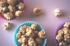 Słodki karmelu popkorn w kolorowych filiżankach Zdjęcia Stock