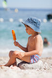 Słodki małe dziecko, chłopiec, je lody na plaży Fotografia Stock
