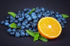 Słodkie czarne jagody z dojrzałą połówką pomarańcze i zieleń wybijają monety Całe czarne jagody z połówką pomarańcze i mennica na Zdjęcie Royalty Free