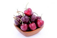 Słodkie wiśnie w drewnianym pucharze odizolowywającym na białym tle fotografia royalty free