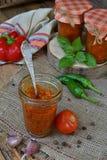 Słoje pomidorowy kumberland z chili, pieprzem i czosnkiem, Bolończyka kumberland, lecho lub adjika, konserwacja konserwowanie zdjęcie stock