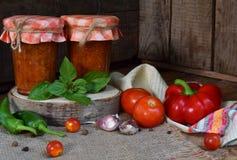Słoje pomidorowy kumberland z chili, pieprzem i czosnkiem, Bolończyka kumberland, lecho lub adjika, konserwacja konserwowanie zdjęcie royalty free