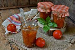 Słoje pomidorowy kumberland z chili, pieprzem i czosnkiem, Bolończyka kumberland, lecho lub adjika, konserwacja konserwowanie zdjęcia royalty free