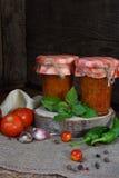 Słoje pomidorowy kumberland z chili, pieprzem i czosnkiem, Bolończyka kumberland, lecho lub adjika, konserwacja konserwowanie fotografia stock