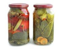 Słoje z kiszonymi ogórkami i pomidorami odizolowywającymi na bielu Zdjęcia Royalty Free