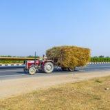 Słoma transport z ciągnikiem na wiejskiej drodze Zdjęcia Stock