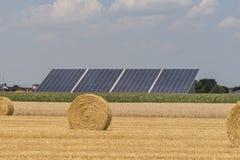 Słomiane rolek bele z uprawy polem, photovoltaic panelem i niebieskim niebem w tle, zdjęcie stock
