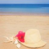 Słomianego kapeluszu ans seashells na piasek plaży Obrazy Royalty Free