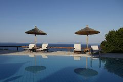 Słomiani plażowi parasole i sunbeds obok basenu zdjęcia royalty free