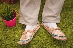 Słomiani sandały na zielonym tle Fotografia Stock