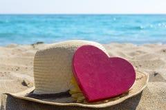 Słomiany kapelusz i kierowy kształt na piaskowatej plaży Fotografia Stock