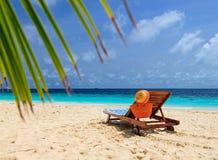 Słomiany kapelusz i torba na holu krześle przy piaskiem wyrzucać na brzeg Zdjęcia Stock