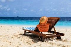Słomiany kapelusz i torba na holu krześle przy tropikalną plażą Zdjęcia Stock