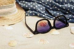 Słomiany kapelusz, przykrywki beachwear opakunek i słońc szkła na tropikalnej plaży, obrazy royalty free