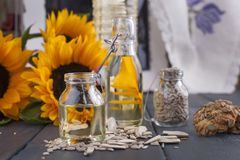 Słonecznikowy olej i ampuła żółci kwiaty blisko okno Olej w butelce Bez łupy słonecznikowi ziarna abstrakcjonistycznego zdjęciu t Zdjęcia Royalty Free