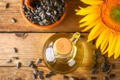 Słonecznikowy olej i słonecznikowi ziarna w małym worku na tradycyjnym nieociosanym drewnianym tle Organicznie i eco jedzenia poj zdjęcia royalty free