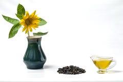Słonecznikowy olej w szklanej sos łodzi, wiązka słonecznikowi ziarna i słonecznik z komarnicą w wazie, Odizolowywający na białym  zdjęcie royalty free