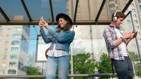Słoneczny dzień, ludzie stojaka przy przystankiem autobusowym z telefonami komórkowymi autobus czeka kamera na steadicame zbiory wideo