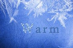 Słowa ciepły pisać na zimy śnieżnym błękitnym tle Zdjęcia Royalty Free