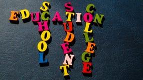 Słowa edukacje, szkoła, uczeń, szkoła wyższa budowali kolorowi drewniani listy na zmroku stole Obrazy Stock