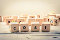 Słowa ` kosztu ` drewniany Kubiczny na drewnie zdjęcia royalty free