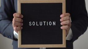 Słowa rozwiązanie od listów na tekst desce w anonimowych biznesmen rękach zdjęcie wideo