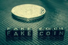 Słowa sfałszowana moneta czarni sześciany i srebna moneta na szarości fotografia royalty free