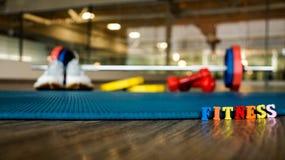 Słowa ` sprawności fizycznej ` buduje kolorowi drewniani listy z zamazanym wspiera dumbbell, działających buty, ciężary i matę, Fotografia Stock