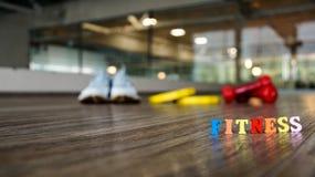 Słowa ` sprawności fizycznej ` buduje kolorowi drewniani listy z zamazanym wspiera dumbbell, działających buty i talerze, Fotografia Royalty Free