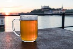 Słowacki piwo 0,5 litrów na drewnianym stole na tle rzeczny Bratislava i Danube roszuje przy zmierzchem, Sistani zdjęcie royalty free