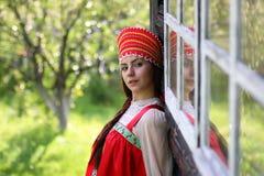 Słowiańska kobieta w tradycyjnej smokingowej drewnianej ścianie obrazy stock