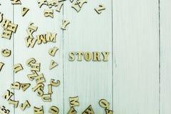 Słowo «opowieść «na białym tle, rozrzuceni drewniani listy ilustracji