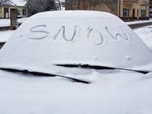 Słowo śnieg pisać na śnieżystym samochodowym okno Śnieżyści samochody w zimie Zimna pogoda Brudny drogowy ruch drogowy zdjęcia royalty free