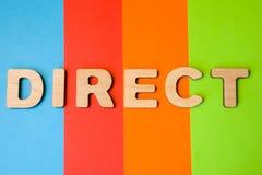Słowo Bezpośredni wielcy drewniani listy na barwionym tle 4 koloru: błękit, pomarańcze, czerwień i zieleń, Fotografia lub symbol  Obraz Stock