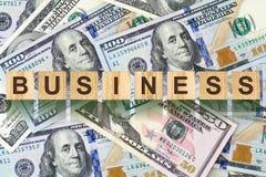 Słowo, biznes komponował listy na drewnianych elementach przeciw tłu dolarowi rachunki Pojęcie biznes, finanse Zdjęcie Stock
