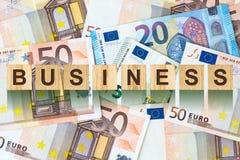 Słowo, biznes komponował listy na drewnianych elementach przeciw tłu Euro banknoty Pojęcie biznes, finanse Zdjęcia Stock