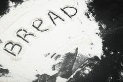 Słowo chleb napisze na stole z mąką zdjęcia royalty free