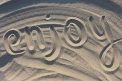 Słowo cieszy się patroszonego na piasku w zmierzchu świetle słonecznym i być na wakacjach tło jak relaksuje Fotografia Stock