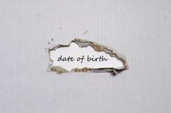 Słowo data urodzenia pojawiać się za poszarpanym papierem Obrazy Royalty Free
