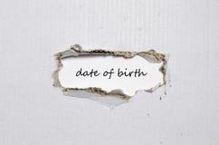 Słowo data urodzenia pojawiać się za poszarpanym papierem Obraz Royalty Free