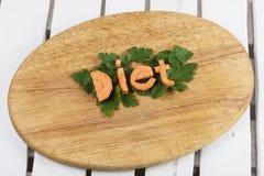 Słowo dieta od marchewek na tnącej desce Zdjęcie Royalty Free