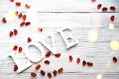 Słowo drewniani listy, miłość z czerwonymi szklanymi kamieniami fotografia stock