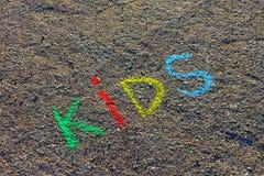 Słowo dzieciaki pisać z kolorowymi kredkami na asfalcie, ziemia Obrazy Royalty Free