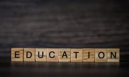 Słowo edukacja, składać się z lekcy drewniani kwadratowi panel dalej obrazy stock