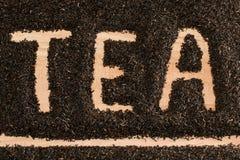Słowo herbaty palec rysujący w stosie czarni herbaciani liście Obraz Stock